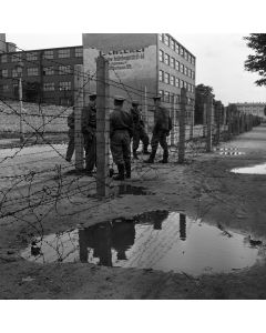 East German Volkspolizei guard the barbed wire fence that separates East and West Berlin